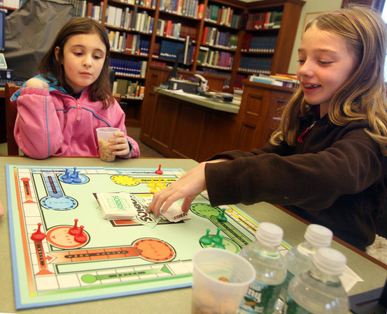 """Manchester: Bella Leonard, right, smiles as she draws a """"Sorry!"""" card, sending one of Elizabeth Staid's pieces back to the start as they play board games at the Manchester Library on Tuesday afternoon. Photo by Kate Glass/Gloucester Daily Times"""