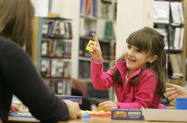 Essex: Kendall Newton, 5, shows librarian April Wanner who her mystery person was while playing Guess Who during library game day at the TOHP Burnham Library Friday afternoon. Mary Muckenhoupt/Gloucester Daily Times