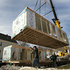 Gloucester: The second piece of Wayne and Carol Jackson's new home gets lifted into place on Eastern Avenue Friday morning.  The Jackson's home was severly damaged after the home of their neighbor Wayne Sargent exploded last january. Mary Muckenhoupt/Gloucester Daily Times