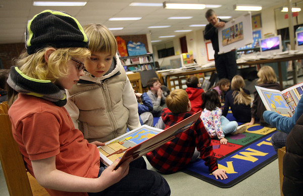 "Rockport: Gus Johnson, left, and Levin Rudler, both 6, look through the book, ""What's Inside?"" as author/illustrator Giles Laroche shows the original illustrations to the crowd gathered at the Rockport Elementary School Library for the Raising Rockport Readers Author Night program on Thursday. Photo by Kate Glass/Gloucester Daily Times"