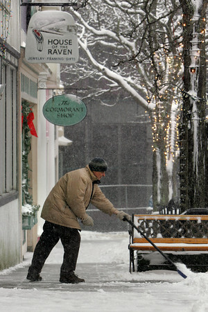 Gloucester: Theo Taminiau tries to keep up with the snow as he clears the sidewalk in front of his store House Of The Raven on Main Street Saturday afternoon. Mary Muckenhoupt/Gloucester Daily Times