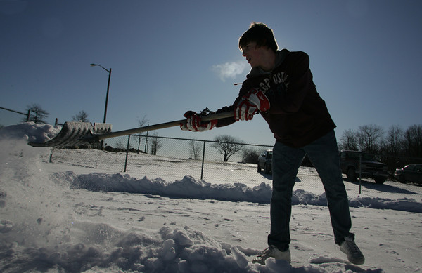 Gloucester: John Jermyn, 17, shovels the basketball courts at Stage Fort park with some of his friends so the court can be used for street hockey Saturday afternoon. Mary Muckenhoupt/Gloucester Daily Times