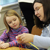 Essex: Kate O'Neill 5, watchs Margaret Soucy cast on during knitting lessons given at the TOHP Burnham Public Library Wednesday afternoon.  After Kate practiced a bit her mom, Beth, also picked up the knitting needles to learn how to knit. Mary Muckenhoupt/Gloucester Daily Times