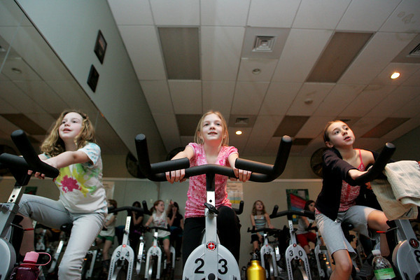 Manchester: From left, Sydney Ring, Juliette Kelley and Zoe Ducroux keep peddling with their fellow Girl Scouts from Manchester troop 66304 during a spinning class at the Manchester Athletic Club Friday afternoon.  The fouth grade girls took the class to work toward earning a badge. Mary Muckenhoupt/Gloucester Daily Times