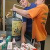 "Essex: Evan Pennoyer, left, and Logan Carroll add change to the ""Coins for Care"" collection at Essex Elementary School yesterday afternoon. Money and medical supplies the school collects will go to Ipswich-based Partners in Development, which is sending staff and volunteers to Haiti to help earthquake survivors. Photo by Kate Glass/Gloucester Daily Times"