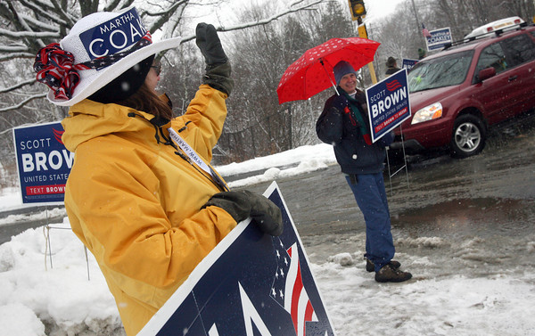 Manchester: Michele Kulick and Polly Townsend wave to voters in front of Manchester Memorial Elementary School yesterday afternoon, urging them to cast their ballots for their respective candidates. Photo by Kate Glass/Gloucester Daily Times