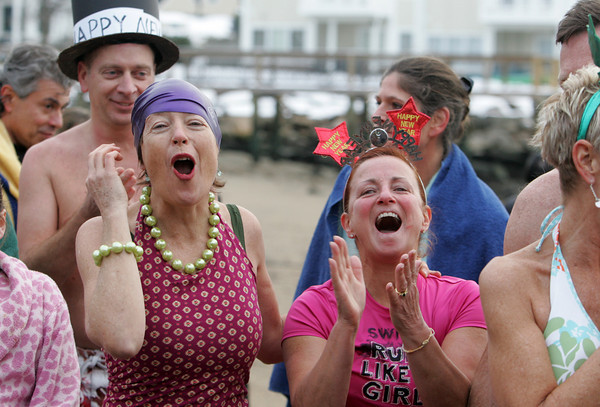 Gloucester: Margi Green and Nanci Bishop cheer after George Sibley read his annual poem before the New Year's Day swim at Oak Grove Beach on Rocky Neck Friday afternoon.  Once the poem has been read then it's a coutdown before running into the water. Mary Muckenhoupt/Gloucester Daily Times