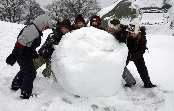 Gloucester: Jackson Wood, Carl Parkhurst, Peter Wood, Luke Pata, Sophia Pata, and Julia Wood roll a large snowball at Stage Fort Park yesterday afternoon. The two girls started the snowball at Tablet Rock and asked the boys to help out as it grew in size and weight. Photo by Kate Glass/Gloucester Daily Times