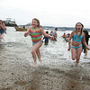 Gloucester: Isabel Gleckner 11, rushes out of the water at Oak Grove Beach after the New Year's Day swim on Rocky Neck Friday afternoon.  Adults  and many children braved the cold water to start 2010 with a refreshing dip in the ocean. Mary Muckenhoupt/Gloucester Daily Times