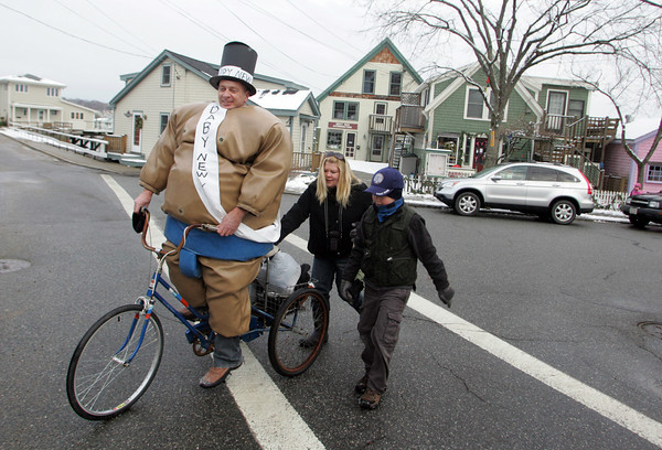 Gloucester: Scott Levasseur gets a push from his son Fisher and wife Lisa as they head to Oak Grove Beach for the annualNew Year's Day swim at Rocky Neck Friday afternoon. Mary Muckenhoupt/Gloucester Daily Times