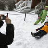 "Gloucester: Amy Gallagher takes a picture of Sarah Werner, 9, Matthew Werner, 6, and Samantha Sullivan, 9, with the snowman they made  in their front yard on Maplewood Avenue yesterday afternoon. ""We've had this snowman kit for a while and were finally able to use it,"" Gallagher said. The kit came with a hat, scarf, coal, and a plastic carrot nose. Photo by Kate Glass/Gloucester Daily Times"