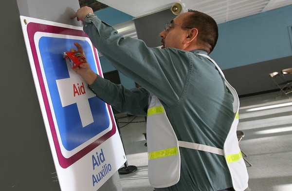 Gloucester: Jack Vondras, Gloucester Health Director, hangs up signs around the Fuller School Cafeteria before the flu clinic yesterday afternoon. Volunteers arrive several hours before start time to set up for the clinic. Photo by Kate Glass/Gloucester Daily Times