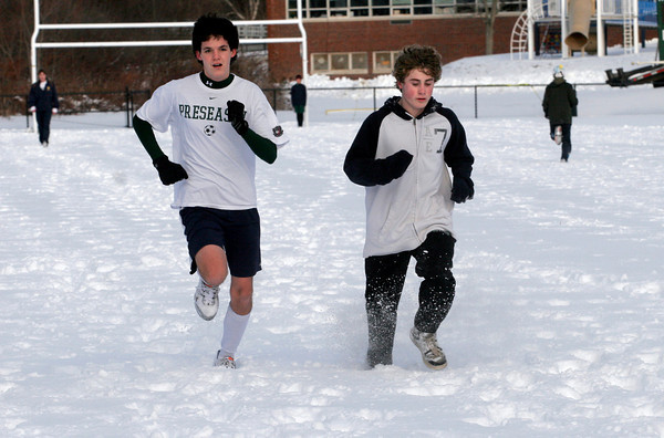 Manchester: Sam Cushing, left, and Stephan Laforge, right, run across Coach Ed Field Field in the snow as part of their sprinters workout for track. Photo by Kate Glass/Gloucester Daily Times Monday, January 4, 2009