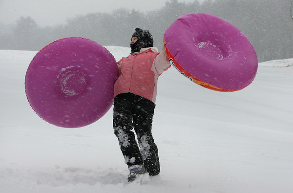 Manchester: Haley New, 9, almost gets blown away while holding her and her sister Lexi's innertube while sledding at the Essex County Club Saturday afternoon.  Mary Muckenhoupt/Gloucester Daily Times