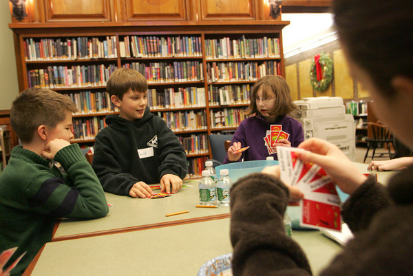 Manchester: From left, Charles Davis, David Reid, Hannah Sinclair and Sophia Wilson, front, play Apples to Apples during Lock-in Game Night at the Manchester Public Library Friday evening.  The library closes at 5 so kids had to be there at 4:30 so they could start the game before the doors to the library locked for everyone else. Mary Muckenhoupt/Gloucester Daily Times
