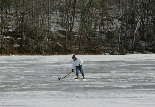Gloucester: A man pushes a puck around on West Pond in Magnolia Saturday afternoon. Mary Muckenhoupt/Gloucester Daily Times