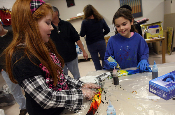 Rockport: Brooke Demeri points out her favorite part of her tie-dye shirt to Ali Ketchopulos as they color Raising Rockport Readers t-shirts at the Rockport Elementary School on Thursday. Photo by Kate Glass/Gloucester Daily Times