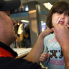 Gloucester: Gloucester paramedic Jason Lococo gives the nasal H1N1 vaccine to Megan Merchant, 5, of Gloucester during the clinic at the Fuller School yesterday. There is always at least one paramedic at each flu clinic to help with the pediatric vaccines and in case anyone has an immediate reaction to the vaccine. Photo by Kate Glass/Gloucester Daily Times