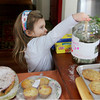 Gloucester: Gracie Burbank, 3, of Rockport places money int he donations jar at the bake sale for Haiti relief at the home of Gina Fettig on Stockholm Road Thursday afternoon. The bake sale, which went from 10 a.m. to 5 p.m. raised $1,300. Mary Muckenhoupt/Gloucester Daily Times