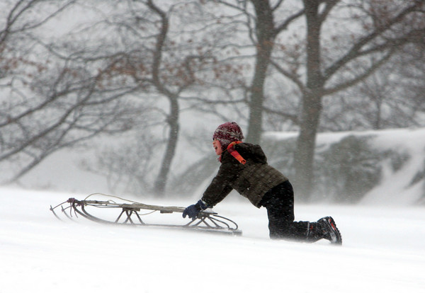Gloucester: Owen Bryan, 8, of Gloucester pushes his sled up a very windy hill at Stage Fort park while sledding with his family Saturday afternoon.  Mary Muckenhoupt/Gloucester Daily Times