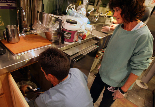 Gloucester: Maryellen Borge watches as her husband, Joe, removes the ceramic cartridge from their water filtration system at Lone Gull Coffeehouse to clean it. The business lost $20,000 while they were forced to close during the boil water this summer. Photo by Kate Glass/Gloucester Daily Times