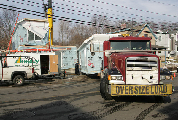 Gloucester: The forth and last piece of the Wayne and Carol Jackson's home gets delivered on Eastern Avenue Friday afternoon.  The Jackson's home was severly damaged after the home of their neighbor Wayne Sargent exploded last january. Mary Muckenhoupt/Gloucester Daily Times