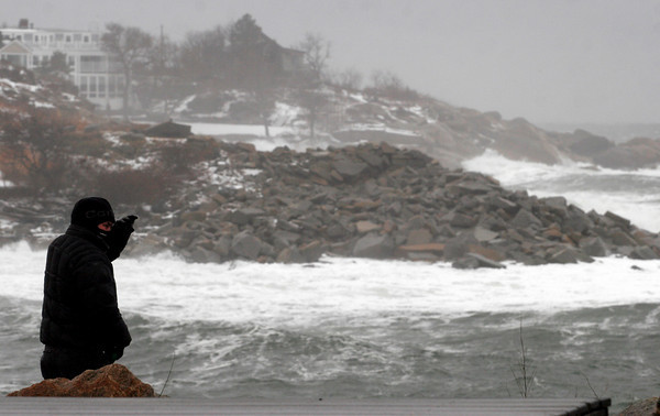 Rockport: Ken Belanger shields his face from the sea spray as he checks out the waves from Granite Pier yesterday afternoon. The wind was gusting around 30 m.p.h. Photo by Kate Glass/Gloucester Daily Times