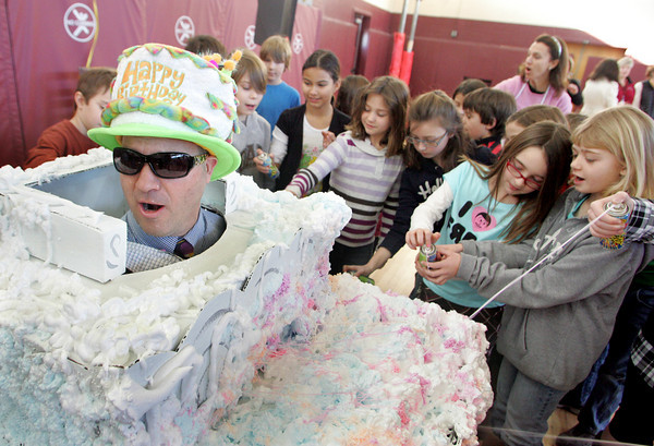 Rockport: Shawn MaGuire, principal of the Rockport Elementary School, turns his face as second graders spray him with silly string in the school's gymnasium Thursday morning. MaGuire won a principal's challenge in a contest sponsored by Stop & Shop, in which he promised to turn himself into a human birthday cake for which the school would received $1,000 as part of the supermarket's A + Bonus Bucks program.  Each student got a chance to help decorate the giant cake with such ingredients as shaving cream, silly string, confetti, and giant candles. Mary Muckenhoupt/Gloucester Daily Times