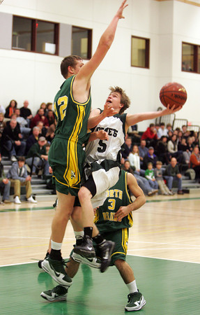 Manchester: Manchester Essex guard Sean Nally shoots over North Reading's Jeffrey Tyner during the basketball game at Manchester Essex Regional High School Friday night. Mary Muckenhoupt/Gloucester Daily Times