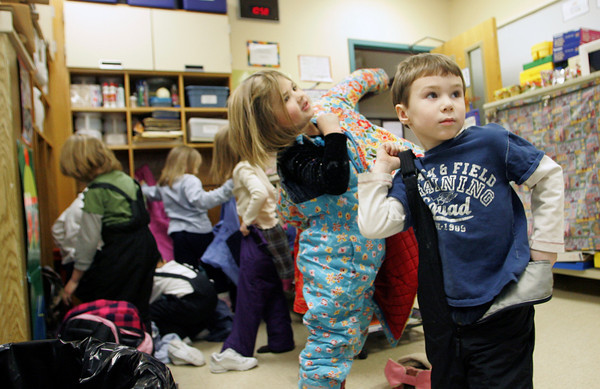 Rockport: Logan Ketchopules puts on his snow pants with the the rest of his kindergarten classmates in Sue Niemi's classroom Thursday afternoon. The kids put their snow pants on to wear to lunch so they can be ready to play outside for recess. Also pictured is Kylie Schrock, back.  Mary Muckenhoupt/Gloucester Daily Times