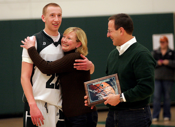Manchester: Manchester Essex's Joe Mussachia hugs his mom, Sara, as his dad, John, presents him with a plaque during a ceremony to celebrate Joe scoring his 1,000th point during the Hornets' game against Wilmington last night. Photo by Kate Glass/Gloucester Daily Times