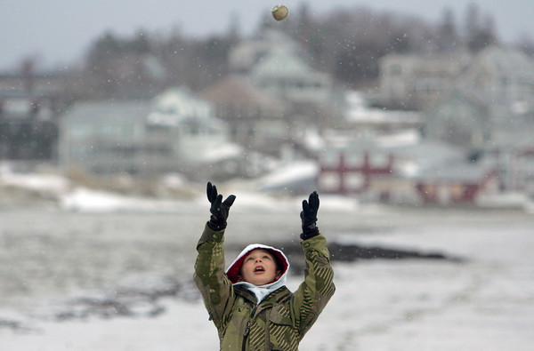 Gloucester: Jaiden Ciarmataro throws an old tennis ball up in the air while walking his dog with his parents at Good Harbor Beach Friday afternoon. Despite the cold temperature and snow flurries many people were at the beach to give their dogs some exercise.  Mary Muckenhoupt/Gloucester Daily Times