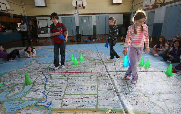 Gloucester: Jacob Allen, Caroline Muniz, and Jemima Grow, all 4th grade students at East Gloucester Elementary School, try to predict where the population will move to in 2100 during a lesson using National Geographic's Giant Map of North America. The program was brought in by the East Gloucester Elementary School PTO and all grades will be working on different lessons with the map. Photo by Kate Glass/Gloucester Daily Times