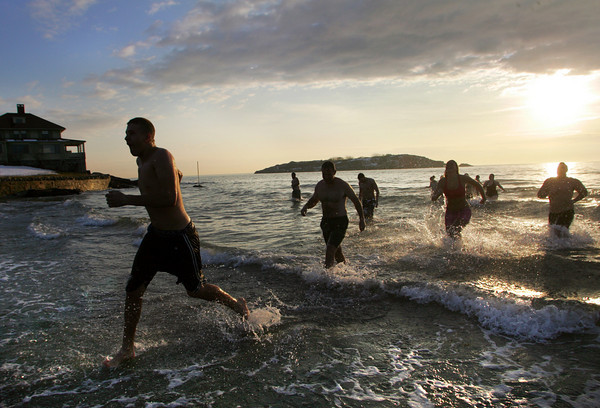 Gloucester: Teddy Flint runs for dry land as people rush out of the cold Atlantic Ocean during the New Year's Day Swim at Good Harbor beach early Saturday morning.  Mary Muckenhoupt/Gloucester Daily Times