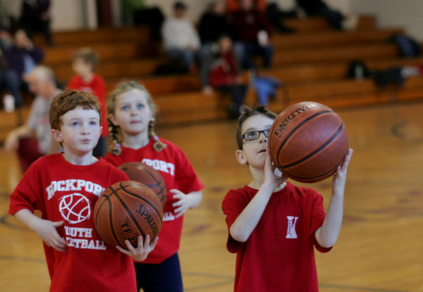 Rockoprt: First grader Zachary Champagne, 7, aims for the basket as Rockport Youth baskaball players run through some basketball drills at Rockport High School Saturday morning. Also pictured is Roy Gebhardt, left, and Skyla Hannon, 7. Mary Muckenhoupt/Gloucester Daily Times