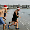 Manchester: Swimmers, including, from left, Thomas Imhoff, David Muller, and Murriam Khambaty run in for another dip after the annual New Year's Day charity swim that took place at Grey Beach in Manchester Saturday. Mary Muckenhoupt/Gloucester Daily Times