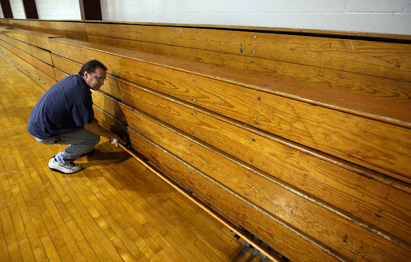 Rockport: Rockport High School custodian Rick Allen struggles to pull out the bleachers in the gym because the boards are warped and stick together. The Capital Improvement Committee is recommending $1.1 million for projects such as replacing the high school bleachers for Fiscal Year 2012. Photo by Kate Glass/Gloucester Daily Times