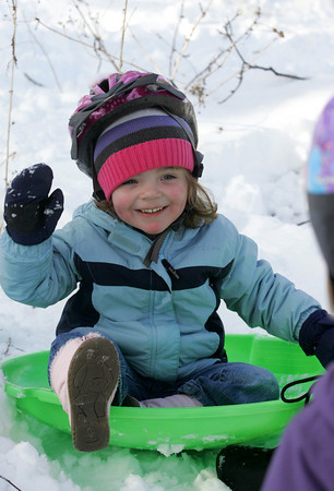 Manchester: Maeve Brooks waves to her cousin after sledding down a hill at her aunt and uncle's house in Manchester Friday morning. Mary Muckenhoupt/Gloucester Daily Times