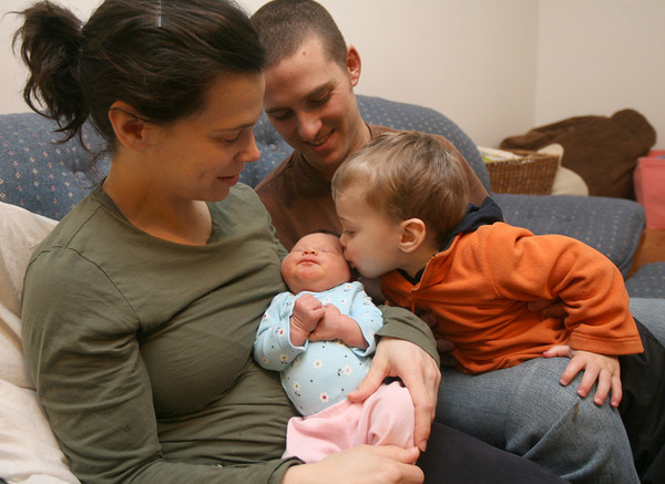 Gloucester: Luke Berthiaume, 20 months, gives his sister, Maggie, a kiss as his mother and father, Natalie and Jason Berthiaume, look on. Natalie gave birth to Maggie on Sunday at their home with the aid of four Gloucester Firefighters. Photo by Kate Glass/Gloucester Daily Times