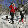 Gloucester: Sally Woodson, front, and Allyson Penaloza cross country ski through Ravenswood Park with Woodson's dog Reeses Thursday afternoon.  Ravenswood Park was filled with crosscountry skiers taking advantage of the freshly fallen snow. Mary Muckenhoupt/Gloucester Daily Times