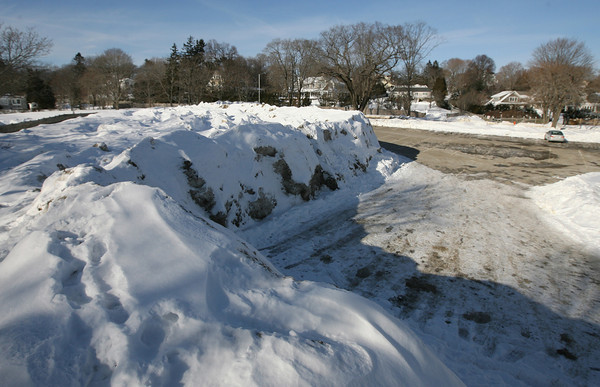 Manchester: Snow piled up from storms so far this winter towers over the parking lot at Singing Beach. Manchester will be implementing cost-saving measures such as only clearing snow during daylight hours and using only DPW crews for snow removal as they are already $100,000 over budget. Photo by Kate Glass/Gloucester Daily Times