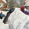 Manchester: Caroline Chrzanowski, 4, takes a turn sliding down a snow luge that her dad, Dave, made in their front yard on Vine Street in Manchester Saturday morning. Also pictured is, from left, Mary Annabel, 6, mom Kathleen, and Luke, 2. Mary Muckenhoupt/Gloucester Daily Times