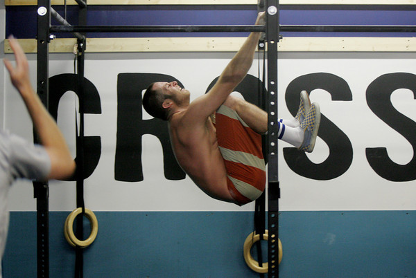 Gloucester: Jon Conant, who runs Crossfit Cape Ann with his wife Karen, pulls his knees up to his chest while running though a half hour intense workout during one of his classes. Mary Muckenhoupt/Gloucester Daily Times