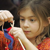 Essex: Samantha Turner, 7, concentates on her knitting during the Learn to Knit program offered at the TOPH Burnham Library Wednesday afternoon. Mary Muckenhoupt/Gloucester Daily Times