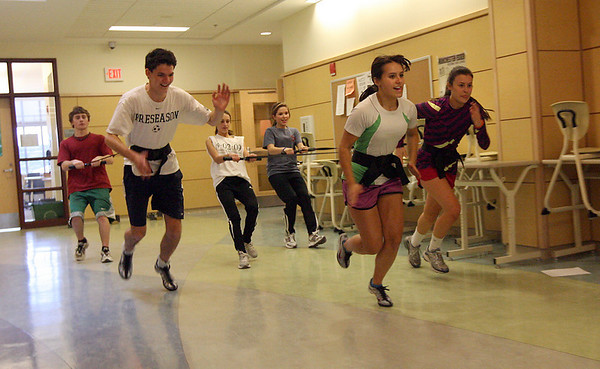 Manchester: Sam Cushing, Anya Ciarametaro, and Maddi Bistong try to run as fast as they can while being held back by Stephen LaForge, Sophia Mastendino, and Mia Rodier during track practice yesterday. Because the school has no indoor track, they use the hallways of the school. Photo by Kate Glass/Gloucester Daily Times