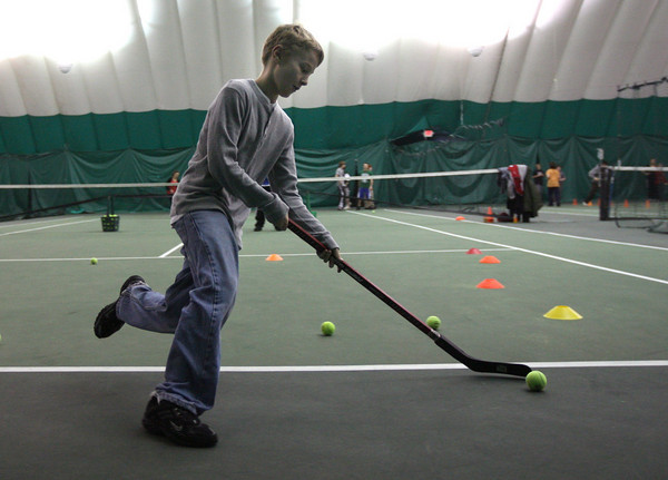 Charlie Sumner, a seventh grade student at O'Maley Middle School, keeps a tennis ball away from obstacles as he and his classmates participate in the free Enrichment Program at the Manchester Athletic Club on Wednesday. The program teaches students about excercise, nutrition, and science. Photo by Kate Glass/Gloucester Daily Times