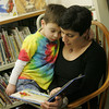 Essex: Liam Turner, 4, of Essex snuggles in with his mom Erin to read a book at the TOHP Burnham Library Wednesday afternoon.  Mary Muckenhoupt/Gloucester Daily Times
