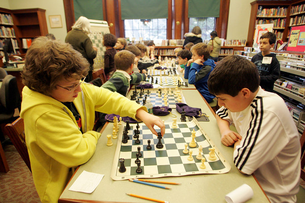 Manchester: Lillian Schrafft, 12, left and Nicholas Curcuru, 11, play a friendly game of chess as the Chess Club meets at the Manchester Public Library Thursday afternoon.  The Chess Club is a four week program, ending next week, that offers learning, playing and prizes the final week and is taught by Sandra Stolle. Mary Muckenhoupt/Gloucester Daily Times