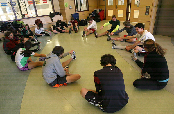 Manchester: Members of the Manchester Essex track team stretch in the hallway outside the cafeteria before practice yesterday. Photo by Kate Glass/Gloucester Daily Times