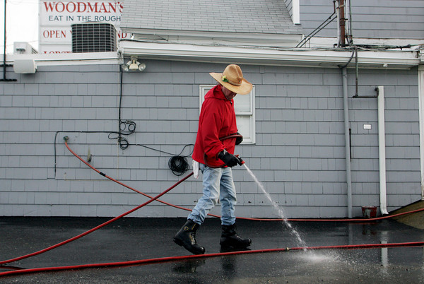 "Essex: Don MacIntyre hoses down the sand and rocks that washed up in front of Woodman's Restaurant Saturday morning. MacIntyre said, ""You have to keep the outside of the place as clean as the inside,"" which was something his grandfather always told him. Mary Muckenhoupt/Gloucester Daily Times"